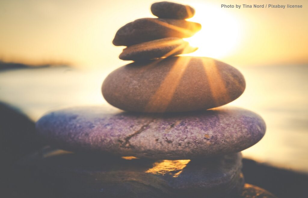 Rocks are stacked from largest to smallest with golden rays of sunlight slanting past. Behind them in a soft focus, the sun sinks into the sea.